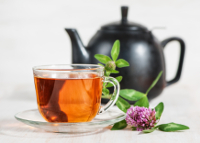 Cup of tea, teapot and branch of clover on wooden background